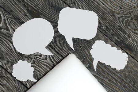 Speech bubbles on a background of brushed pine boards. The edge of the blogger's laptop is visible.