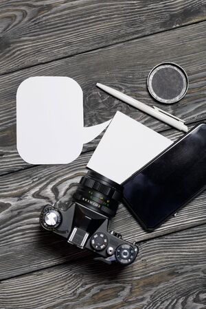 Smartphone and camera blogger. Near a notebook and pen. Around speech bubbles. Against the background of brushed pine boards.