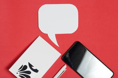 Smartphone blogger. Near a notebook and pen. Around speech bubbles. Against the background of coral color.
