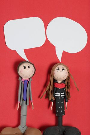 Speech bubbles above the heads of figures of a man and a woman. Against the background of coral color. 写真素材
