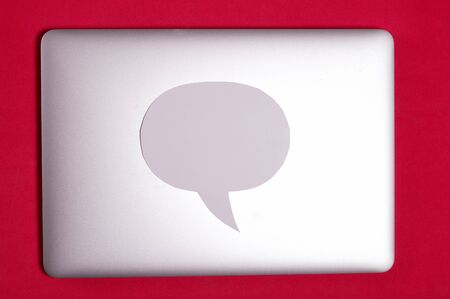 Blogger laptop with a closed lid. A speech bubble lies on the lid. Against the background of coral color.