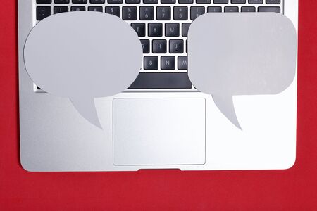 Blogger's laptop. On the keyboard are speech bubbles of different sizes and shapes. Against the background of coral color.