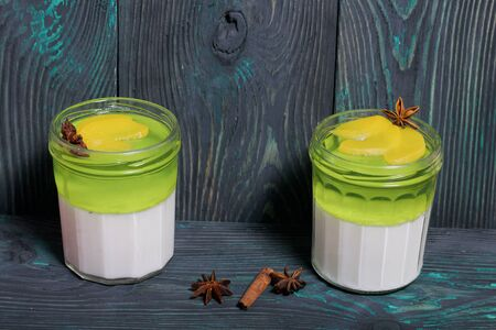 Cream jelly in white and green. Garnished with peach slices and anise star.