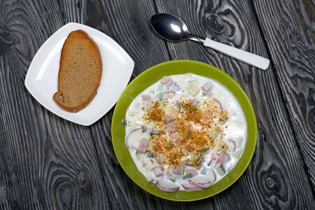 In a plate, chopped vegetables and kefir. Russian dish okroshka with kefir. Near a spoon and a piece of bread.