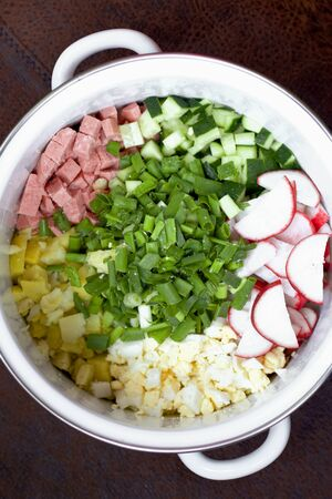Okroshka with kefir. Russian dish. Sliced vegetables are visible in the pan. Shot from above.