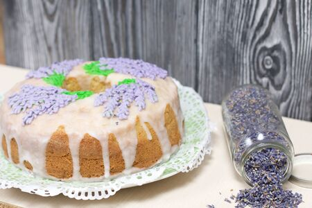 Lavender Cupcake. Sugar coated. Decorated with lavender glaze flowers. Near the bank with lavender inflorescences. 写真素材