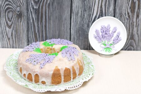 Lavender Cupcake. Sugar coated. Decorated with lavender glaze flowers. Near a saucer with a pattern of glaze.