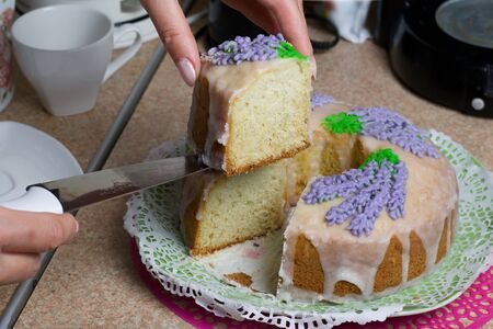 Lavender Cupcake. Sugar coated. Decorated with lavender glaze flowers. A woman cuts a small piece from him. 写真素材
