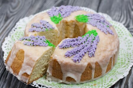 Lavender Cupcake. Sugar coated. Decorated with lavender glaze flowers. A small piece is cut off.