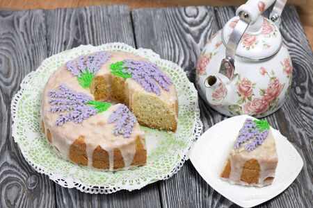 Lavender Cupcake. Sugar coated. Decorated with lavender glaze flowers. A small piece is cut off. Nearby is a kettle. 写真素材