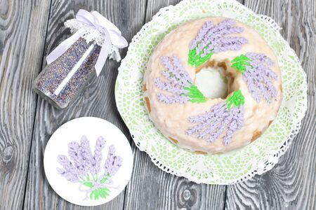 Lavender Cupcake. Sugar coated. Decorated with lavender glaze flowers. Near the bank with lavender inflorescences and a saucer decorated with glaze.