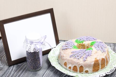 Lavender Cupcake. Sugar coated. Decorated with lavender glaze flowers. Nearby is an empty photo frame.
