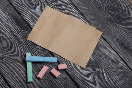 Pieces of chalk for drawing, different colors. Paper. They lie on pine boards painted with white and black paint.
