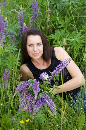Girl sitting in a meadow. Among the blooming lupine. Holding a bouquet in his hands. Stock Photo