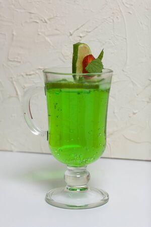 Green lemonade in a glass. Decorated with lime and strawberries. With sprigs of mint. Standard-Bild