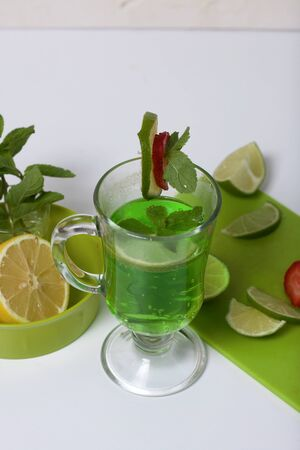 Green lemonade in a glass. Decorated with lime and strawberries. With sprigs of mint. Near lemon and mint.