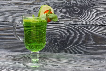 Green lemonade in a glass. Decorated with lime and strawberries. With sprigs of mint. On pine boards.