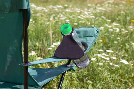 Fragment of a camping chair with a bottle of water and a bouquet. A protective mask hangs on it to protect against the virus. Stands on the grass of a summer meadow.
