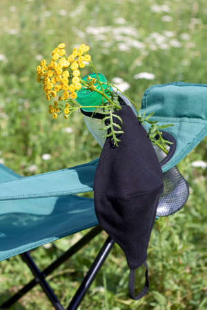 Fragment of a camping chair with a bottle of water and a bouquet of tansy. A protective mask hangs on it to protect against the virus. Stands on the grass of a summer meadow.