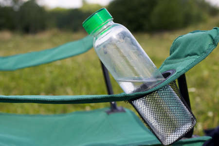 Fragment of a camping chair with a bottle of water and a bouquet. Stands on the grass of a summer meadow. Stockfoto