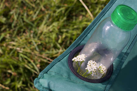 Fragment of a camping chair with a bottle of water and a bouquet of yarrow. Stands on the grass of a summer meadow. Stockfoto