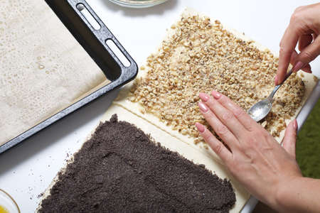 A woman sprinkles a puff pastry with walnuts. For making puff pastry curls with poppy and walnut filling. Nearby on the table are ingredients and tools. 版權商用圖片