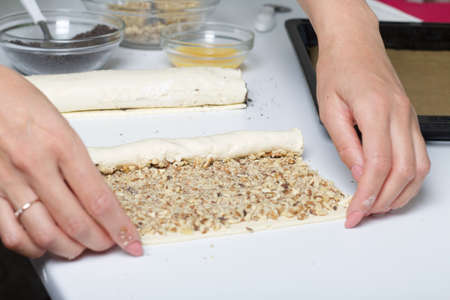 A woman rolls up puff pastry with walnuts into a tube. For making puff pastry curls with poppy and walnut filling. Nearby on the table are ingredients and tools. 版權商用圖片