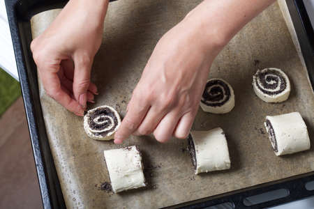 A woman lays curls filled with poppy and walnuts on a baking sheet. Nearby on the table are ingredients and tools.