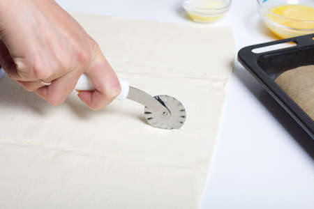 A woman cuts the dough with a pizza knife. For making puff pastry curls with poppy and walnut filling. 版權商用圖片