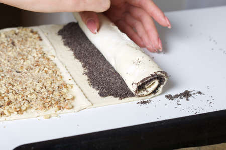 A woman rolls puff pastry with poppy seeds into a tube. For making puff pastry curls with poppy and walnut filling. Nearby on the table are ingredients and tools.