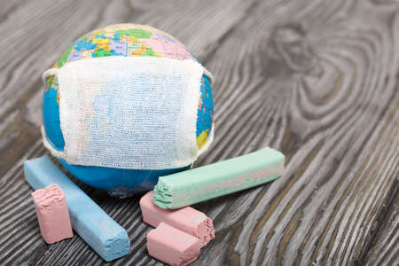 Globe with medical mask. Nearby are crayons. Academic year during the epidemic.