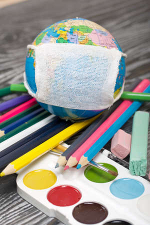 Globe with medical mask. Nearby watercolors, crayons and pencils. Academic year during the epidemic.