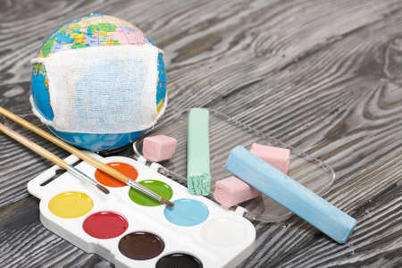 Globe with medical mask. Nearby are crayons and watercolors. Academic year during the epidemic.
