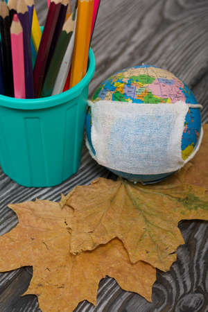 Colored pencils in a pencil holder. Nearby is a globe with a medical mask and dried maple leaves. Academic year during the epidemic.