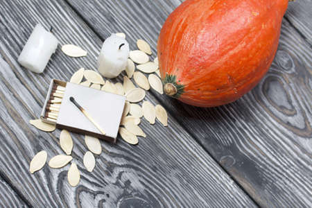 Orange pumpkin, seeds and candle stub. Beside a box of matches. On brushed pine boards painted black and white.
