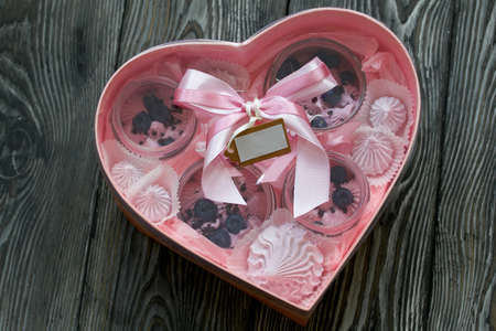 Zephyr in a jar, decorated with blueberries. Packaged in a heart-shaped gift box. On painted pine planks.