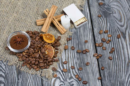 Coffee beans on rough linen and candle stub. Ground coffee in a container and spices. On a surface of brushed pine boards painted black and white.