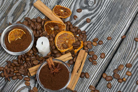 Coffee beans on rough linen and candle stub. Ground coffee in containers and spices. On a surface of brushed pine boards painted black and white.