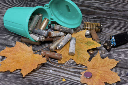 Corroded used batteries. They lie in and around an overturned trash can. Dried maple leaves lie nearby. Disposal of hazardous waste.