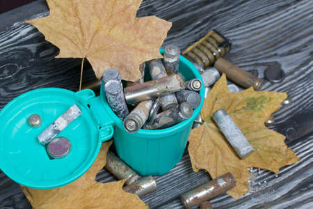 Corroded used batteries. They lie in and around the trash can. Dried maple leaves lie nearby. Disposal of hazardous waste.