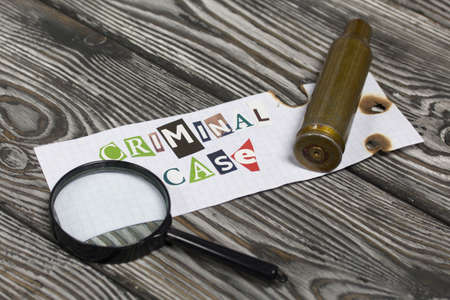 The phrase Criminal case made of letters cut from a magazine and pasted on a sheet of paper. Nearby lies a spent cartridge case and a magnifying glass. On brushed pine boards painted black and white.