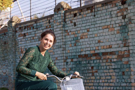 The girl in a green tracksuit. Standing, holding the handlebars of the bike. Against the background of a brick wall.