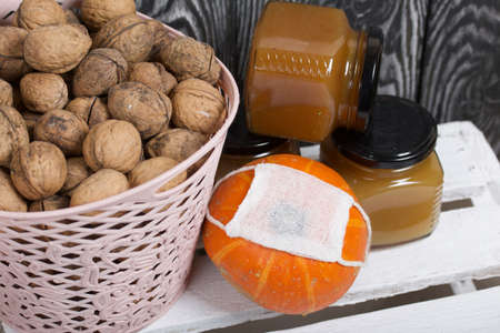 A basket of walnuts and jars of jam. Nearby is an orange pumpkin. They are wearing a medical mask. They stand on a white wooden box.