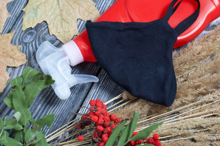 Plastic spray bottle with antiseptic and medical mask. Around is a bouquet of dried grass, rowan branches and dried maple leaves. They lie on black pine boards. 版權商用圖片