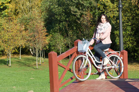 Girl on a bike ride in the autumn park. Crossing a wooden bridge with a bicycle in his hands.