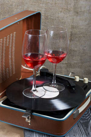 Old turntable. Nearby are two glasses of alcohol. Retro party equipment.
