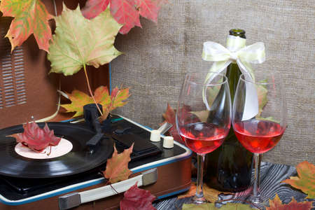 Old turntable. Scattered with autumn maple leaves. Nearby are two glasses and a bottle of alcohol. Retro party equipment.