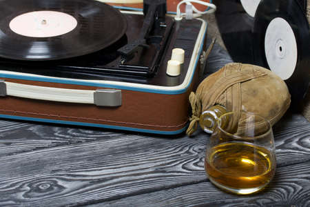 Old turntable. Nearby is a flask and a glass of strong alcohol. Retro party equipment. Archivio Fotografico