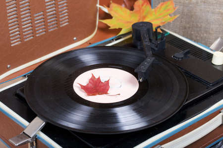 Old turntable. Scattered with autumn maple leaves. Retro party equipment. Archivio Fotografico