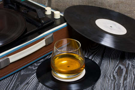Old turntable. Nearby is a glass of strong alcohol. Retro party equipment.